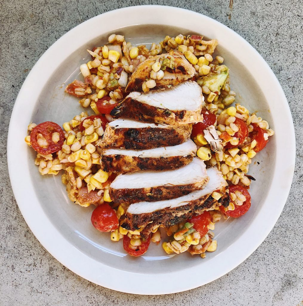 sliced grilled chicken with tomato and corn salad