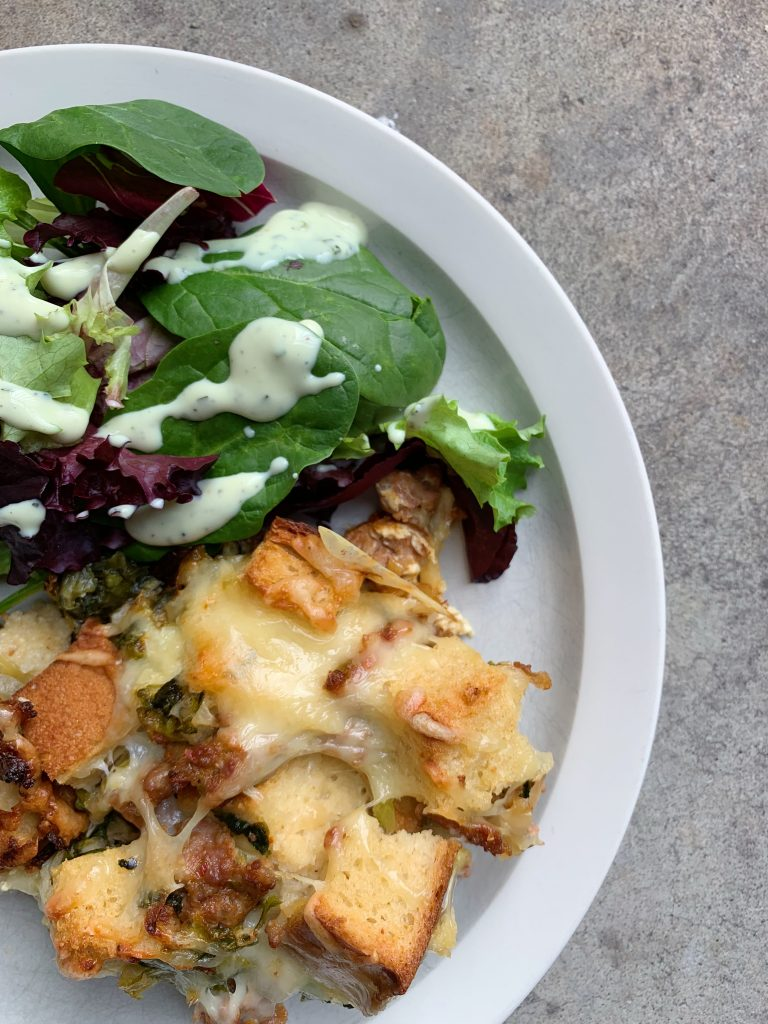 bread pudding with cheese and a leafy green salad